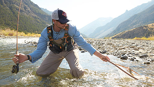 A fisherman catching a trout with an L.L.Bean fly-fishing outfit and net.