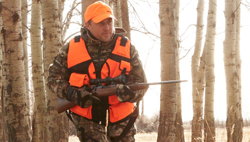 A hunter wearing L.L.Bean's BOA Technical Big-Game Vest and carrying a rifle.