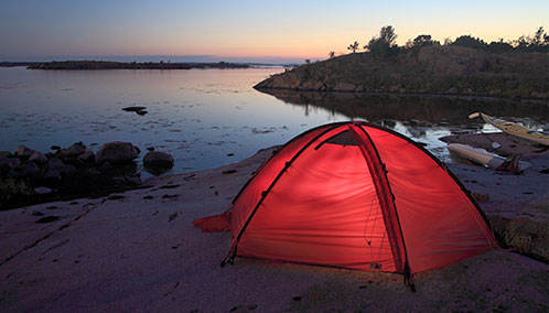 An L.L.Bean tent set up by the shore as the sun sets upon the horizon.