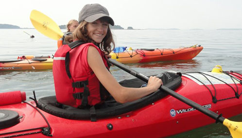 A teenage camper on an island camping adventure outfitted in an L.L.Bean Kayak, paddle and PFD.