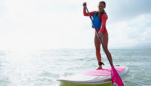 A woman on an L.L.Bean stand-up paddleboard enjoying an adventure on the open ocean.