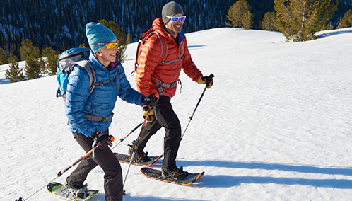 A couple outfitted with L.L.Bean snowshoes, poles and backpacks learning how to snowshoe on a snowshoe adventure.