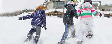 Girl pushing boy in an L.L.Bean snow tube