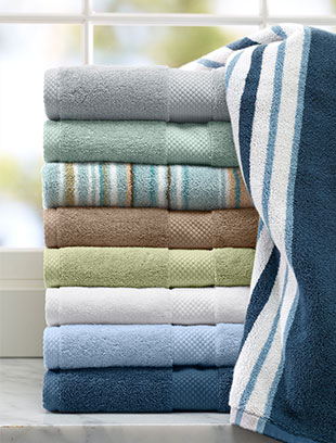 Stack of bath towels in front of window.