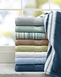 Colorful stack of bath towels on counter in front of bathroom window.
