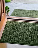 Green Waterhog mats in front of open doorway.