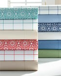 Two colorful stacks of bedsheets in solids, plaids and prints.