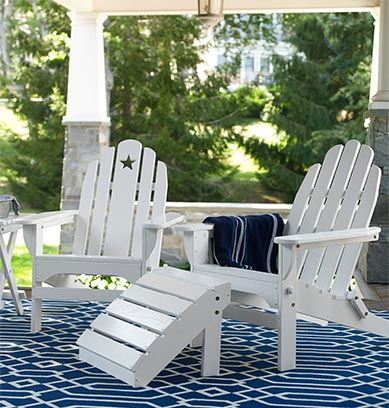 Adirondack furniture on a blue outdoor rug.