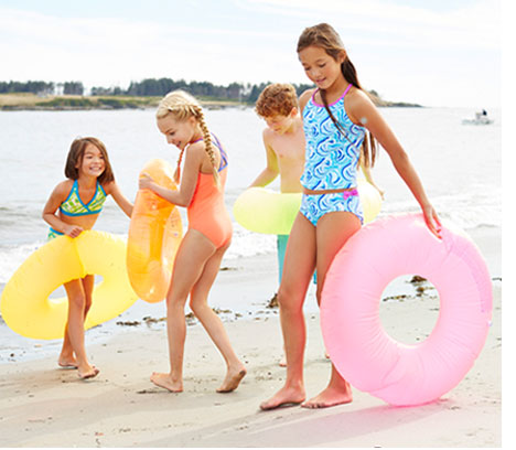 Kids in swimwear on beach.