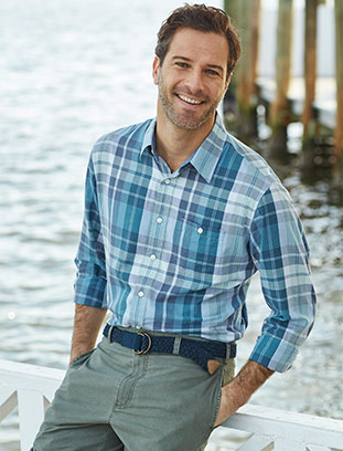 Man by the ocean in a lightweight madras button-down shirt.