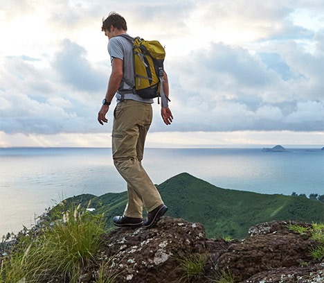 Man in hiking clothing and backpack traversing a ridge by the ocean.