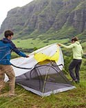 Man and woman putting a rain fly over a backpacking tent.
