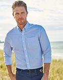 Man by the beach in a blue button-down wrinkle-free shirt.