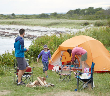 Family camping in a tent near the ocean.
