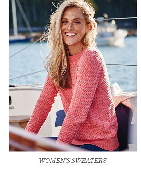 Woman sitting on deck in Coral Rose Basketweave Sweater.