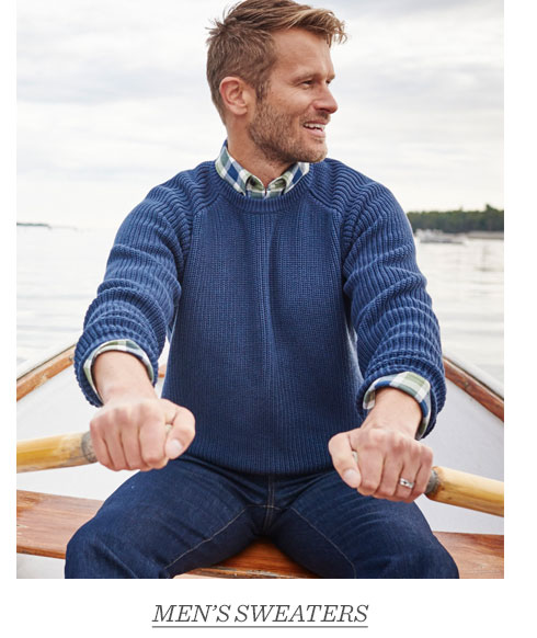 Man in blue sweater rowing a boat.