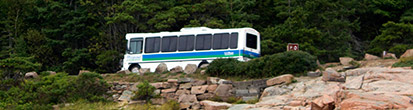 A bus carries its happy passengers on the ocean park loop in Acadia National Park.